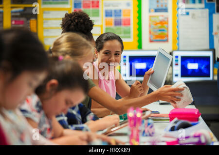 Junior high school girl students using digital tablet in classroom - Stock Image