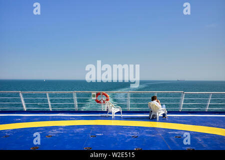 A passenger relaxes in a plastic chair on the rear deck of a cross channel ferry coming into the UK from Brittany - Stock Image