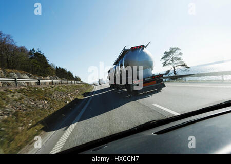 fuel and oil truck driving on freeway, shot from behind through wind screen - Stock Image