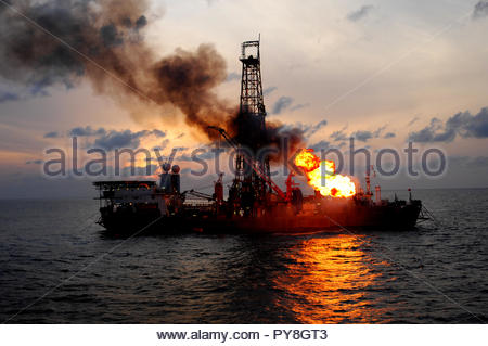 Fire on offshore oil platform at sunset - Stock Image