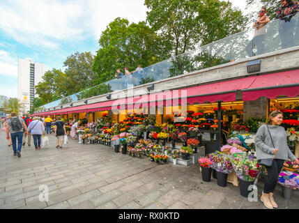 Tourists pass by the busy Tallinn Flower Market on Viru Square, just outside the gates of the Medieval City of Tallinn, Estonia. - Stock Image
