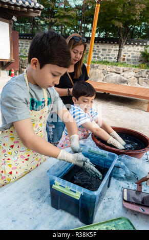 Children tie  dying under the supervision of  their mum at Namsangol Hanok Village, Seoul, South Korea - Stock Image