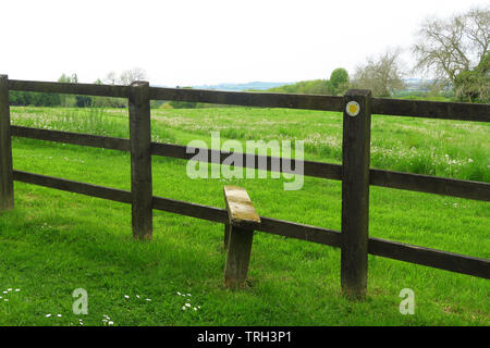 A stile on a footpath together with a 'keep off the grass' warning sign near the north Oxfordshire village of Hook Norton - Stock Image