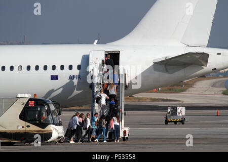 Passengers alighting from airport bus and boarding a jet plane by means of ramp stairs. Holiday travel by air. EU flag visible on rear fuselage. - Stock Image