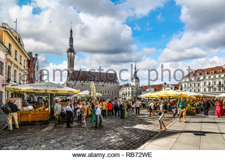 Tourists crowd the sidewalk cafes and shops in the medieval Tallinn Town Square in the walled city of Tallinn Estonia. - Stock Image