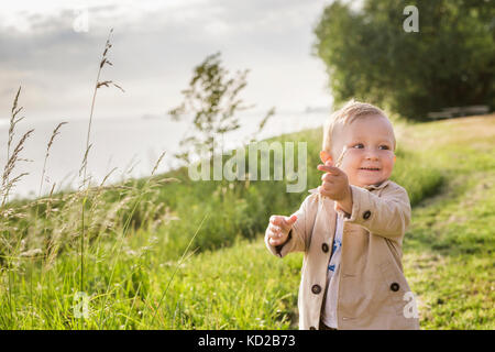 Baby boy (18-23 months) standing by sea - Stock Image