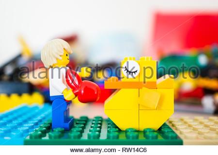 Poznan, Poland - February 15, 2019: Lego man figure feeding a sleeping duck with a apple. - Stock Image