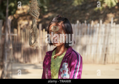Life in the village: portrait of a young girl with typical burmese makeup - Stock Image