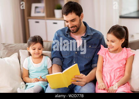 happy father with daughters reading book at home - Stock Image
