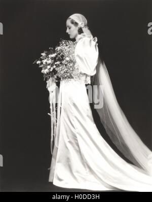 Side view of elegant bride holding bouquet against black background - Stock Image