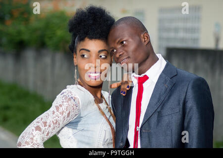 Portrait of happy young couple embracing and standing in the street - Stock Image