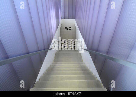 The staircase leading to the bathroom of Bar Luce, Wes Anderson-inspired bar and cafe in the Fondazione Prada district of Milan, Italy - Stock Image