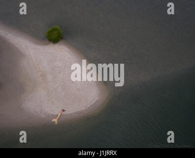 Aerial of a mermaid on a sandbar - Stock Image