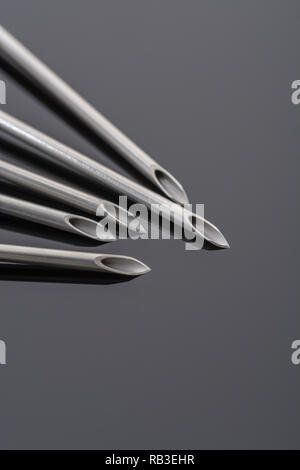 Macro close-up hypodermic needle tips. Specifically BD Microlance  18 Gauge 1 1/2'  1.2/40mm / Pink. Metaphor NHS, innoculation, flu jab, sharp point. - Stock Image