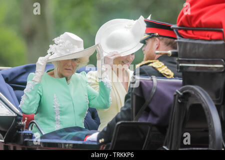 London, UK. 08th June, 2019. HRH Catherine, Duchess of Cambridge and HRH Camilla, Duchess of Cornwall, keep hold of their hats while sharing an open top carriage along The Mall on a windy day. Trooping the Colour, The Queen's Birthday Parade, London UK Credit: amanda rose/Alamy Live News Credit: amanda rose/Alamy Live News - Stock Image