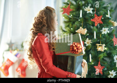 modern woman in red trench coat with shopping bag with Christmas presents near Christmas tree - Stock Image