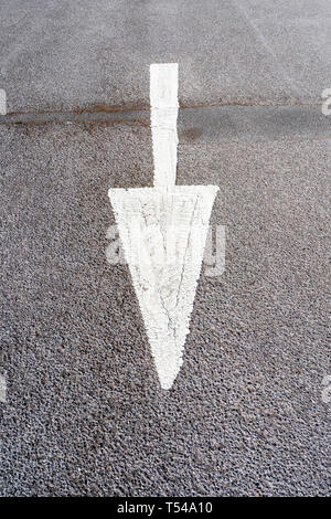 White painted arrow on road surface - Stock Image