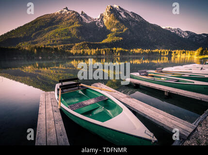 Morning scenery with boats moored on Hintersee lake at sunrise, Bavaria, Germany in summer - Stock Image