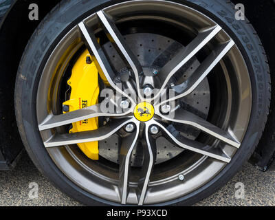 Black Ferrari Sports car detail showing five spoked alloy wheel and disc brake calipers. - Stock Image