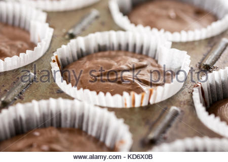 Raw chocolate cup cakes mixture in the cup cakes papers ready for baking. - Stock Image