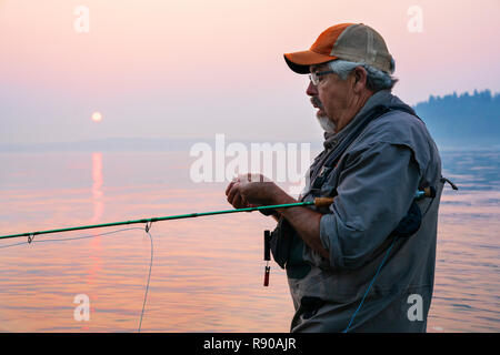 Caucasian man tying a fly on his fly fishing line while fishing for salmon and searun cutthroat trout in Puget Soud near Port Orchard, Washington USA. - Stock Image