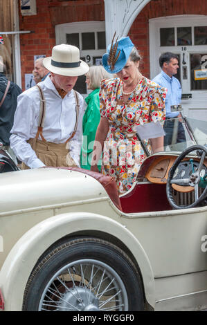 Woodhall Spa 1940s Festival - couple dressed in 1940s outfits at a sports car of that period - Stock Image