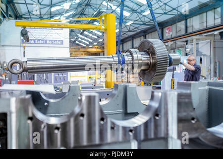 Engineer using crane to position large gear with spindle in gearbox factory - Stock Image