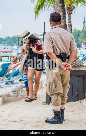 A security guard keeps a watchful eye on tourists at West Bay Beach Roatan Honduras. - Stock Image