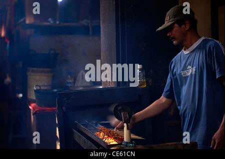 Balinese man cooking chicken satays at Ubud Markets - Stock Image