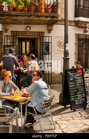 Spain, Jerez de La Frontera, Plaza de Abastos, customers sat at outside bar table in sunshine - Stock Image