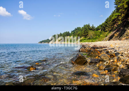 Paradise tropical lagoon with rocky beach blue sky in sunny day - Stock Image