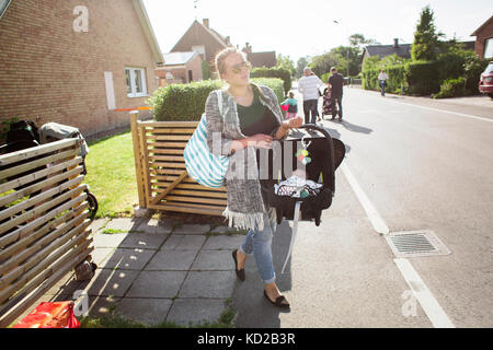 Mother carrying son (0-1 months) in portable car seat - Stock Image