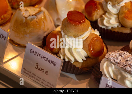 Freshly baked stuffed sweet Sint-Honore pastries in traditinal French bakery in small village in Provence close up - Stock Image