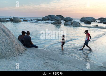 South Africa, Western Cape, Family on the edge of a natural swimming pool (Tidal Pool) at sunset on Camps Bay Beach - Stock Image