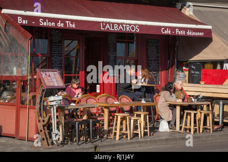 Enjoying the Winter sun outside a bar in Honfleur, Normandy, France. - Stock Image