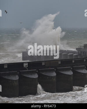 Brighton, UK. 12th Mar, 2019. Waves crash over Brighton Marina western wall this morning as Storm Gareth starts to batter Britain and Ireland with winds expected to reach over 70mph in some areas Credit: Simon Dack/Alamy Live News - Stock Image