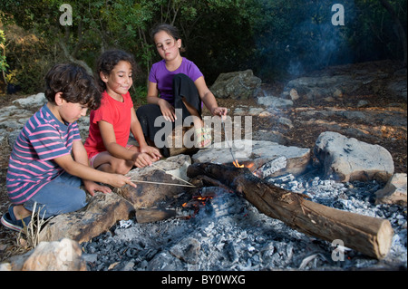 three kids in a campfire in a mediterranean forest - Stock Image