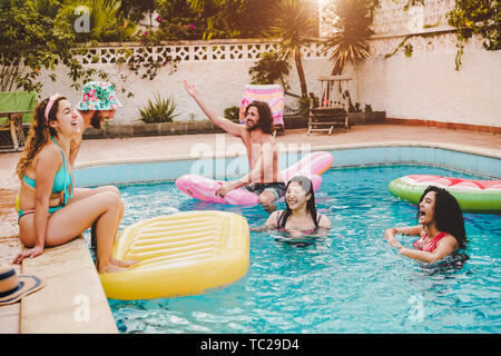 Happy friends having fun in swimming pool during summer vacation - Young people relaxing and floating on air lilo in the pool resort - Stock Image
