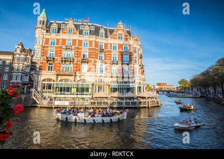 Touristic boats in canal in front of De L'Eeurope hotel - Stock Image