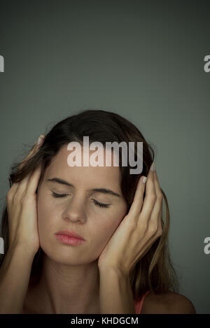 Woman holding hands over ears with eyes closed - Stock Image