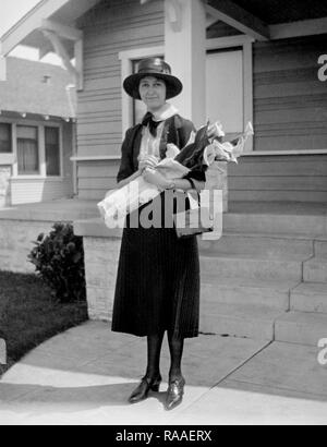 A woman stands with a bouquet of flowers in front of her Colorado home, ca. 1928. - Stock Image