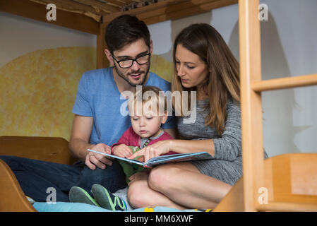 Parents reading a book to their son on the bunkbed, Munich, Germany - Stock Image