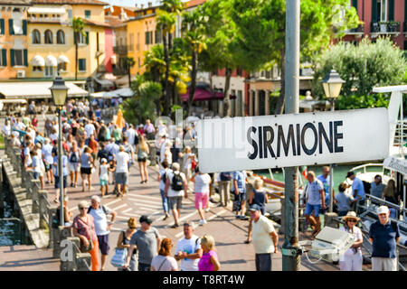 SIRMIONE, LAKE GARDA, ITALY - SEPTEMBER 2018: Signpost on the ferry docking jetty at Sirmione on Lake Garda, with people in the background. - Stock Image