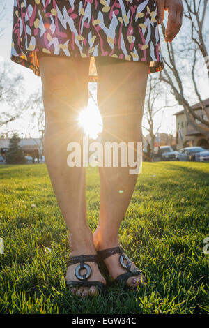 Woman's legs with sun shining between them. - Stock Image