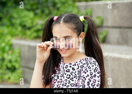 Pretty young girl with her hair in pigtails wearing trendy round sunglasses lowering them to smile happily at the camera outdoors on steps - Stock Image
