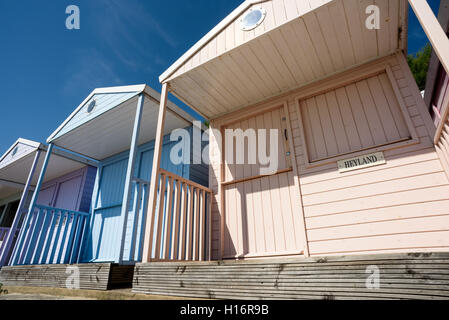 Row of painted summer beach huts with closed doors and windows in summer sunshine. Nobody in the image. - Stock Image