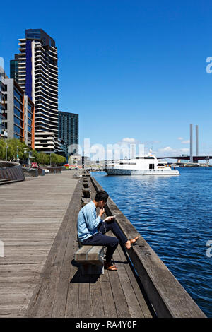 A young Asian man listens to music on his mobile phone in Victoria Harbour in Melbourne Docklands,Victoria Australia. - Stock Image