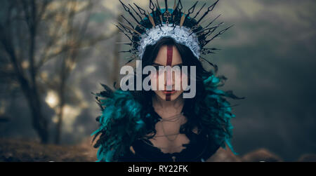 Portrait of young woman in the image of a fairy and a sorceress standing over a lake in a black dress and a crown. - Stock Image