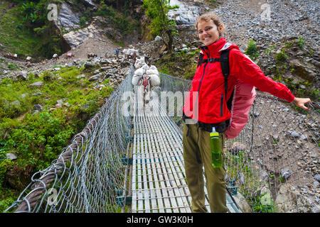 Portrait Young Pretty Girl Wearing Red Jacket Trail Mountains.Mountain Trekking Landscape.Caravan Animal Donkeys - Stock Image