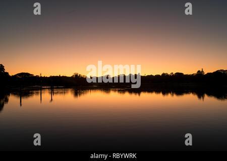 serene sunrise over lake with tree reflections - Stock Image